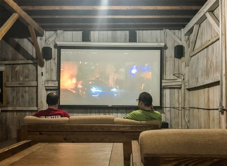 Camp Dewan 88 Two Men Watch Movie On Projector Screen